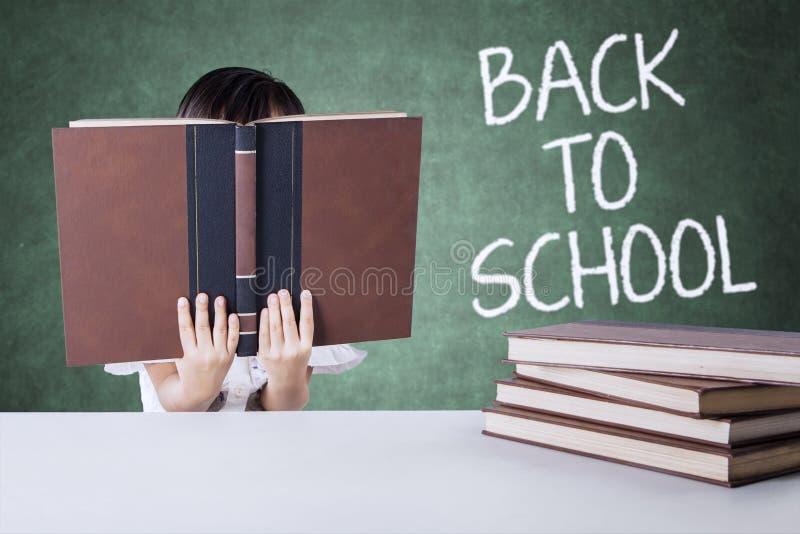Kind terug naar school en gelezen boeken in klasse royalty-vrije stock foto's