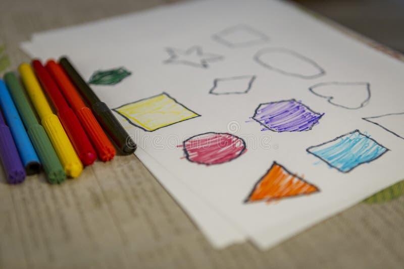 Kind thuis het schilderen en het kleuren cijfers aangaande wit blad stock afbeelding