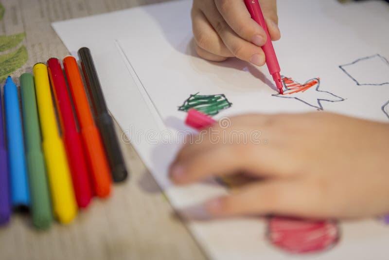 Kind thuis het schilderen en het kleuren cijfers aangaande wit blad stock foto's