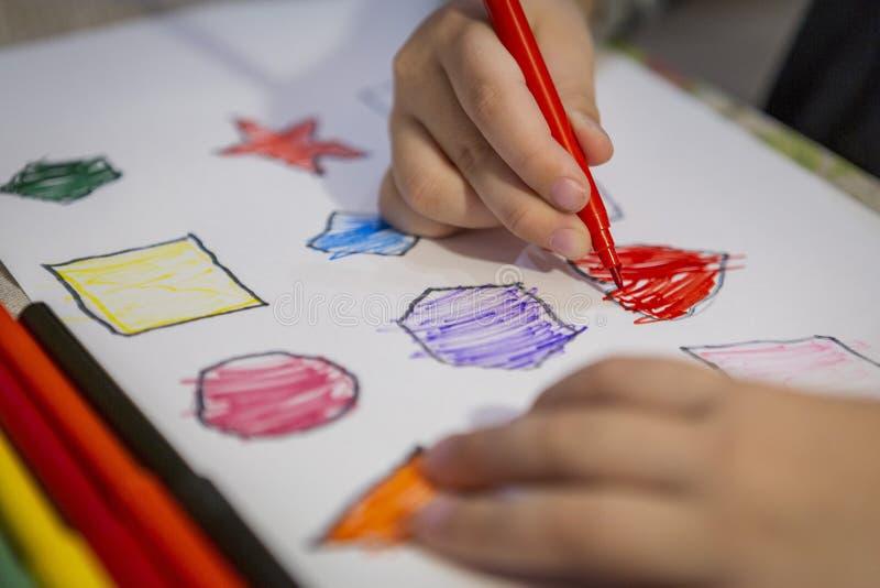 Kind thuis het schilderen en het kleuren cijfers aangaande wit blad royalty-vrije stock foto