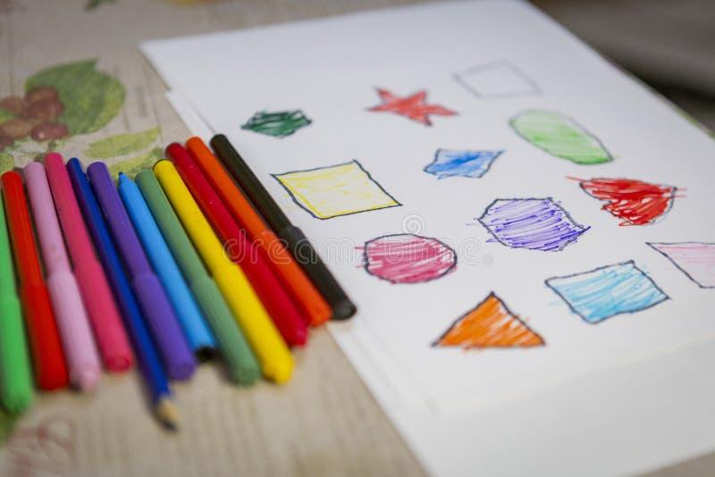 Kind thuis het schilderen en het kleuren cijfers aangaande wit blad stock afbeeldingen