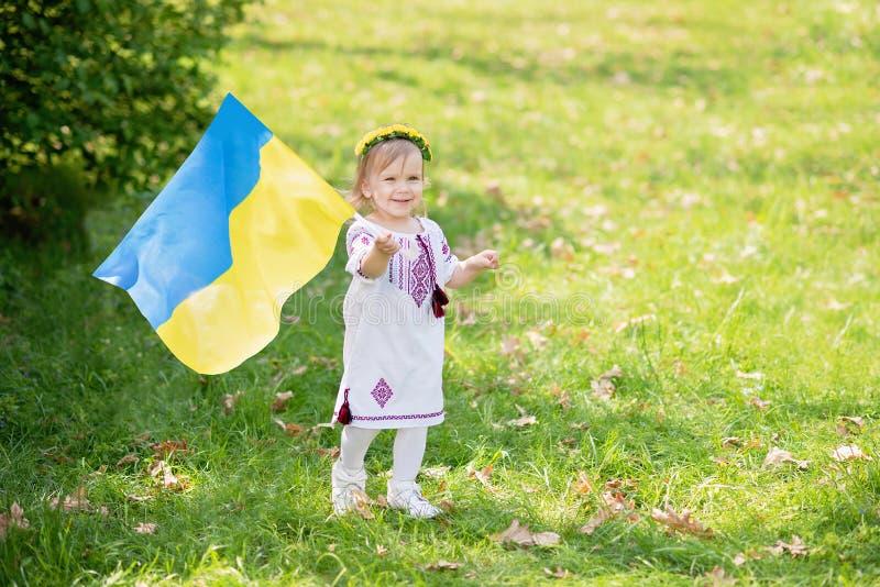 Kind tr?gt flatterndes Blau und gelbe Flagge von Ukraine auf dem Gebiet Ukraine-` s Unabh?ngigkeitstag Feierlicher Hintergrund mi stockbild
