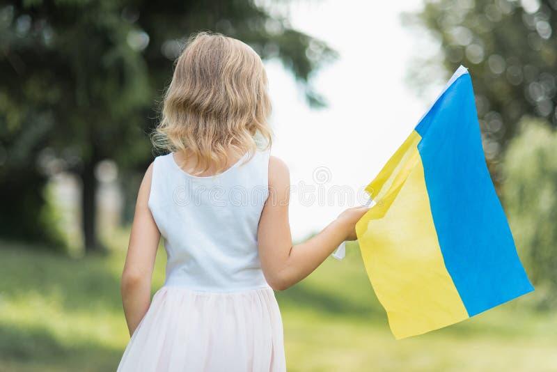 Kind tr?gt flatterndes Blau und gelbe Flagge von Ukraine auf dem Gebiet Ukraine-` s Unabh?ngigkeitstag Feierlicher Hintergrund mi lizenzfreies stockbild