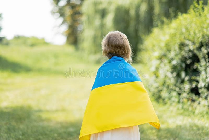 Kind tr?gt flatterndes Blau und gelbe Flagge von Ukraine auf dem Gebiet Ukraine-` s Unabh?ngigkeitstag Feierlicher Hintergrund mi stockfotos