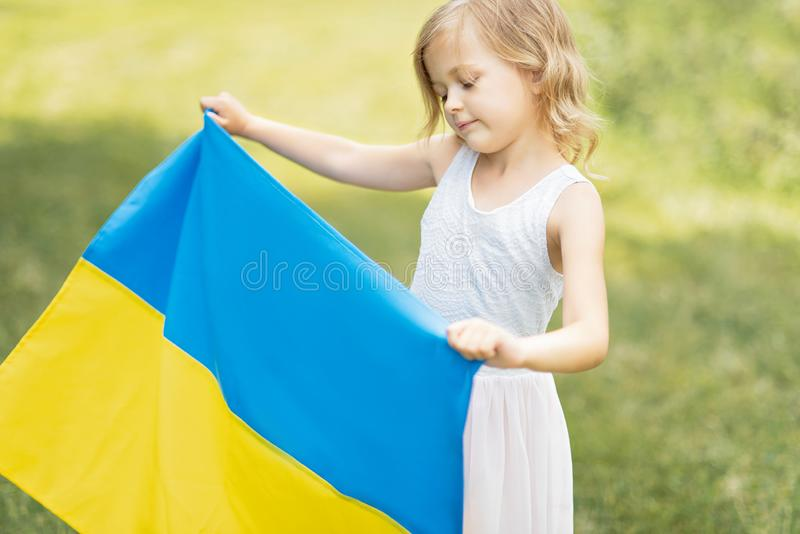 Kind tr?gt flatterndes Blau und gelbe Flagge von Ukraine auf dem Gebiet Ukraine-` s Unabh?ngigkeitstag Feierlicher Hintergrund mi stockfoto
