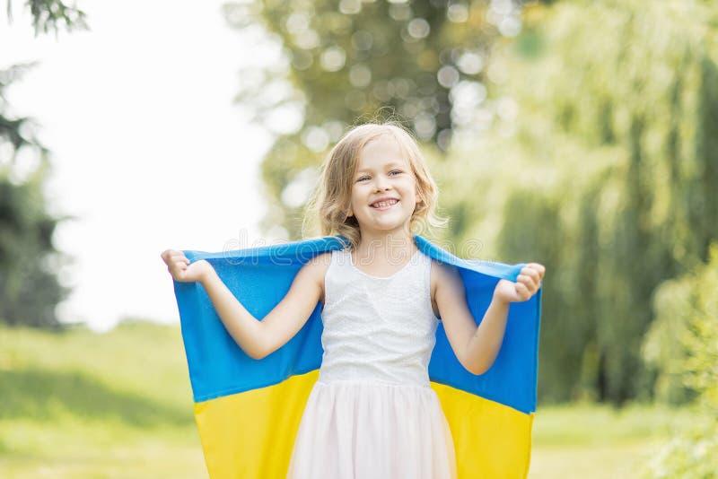 Kind tr?gt flatterndes Blau und gelbe Flagge von Ukraine auf dem Gebiet Ukraine-` s Unabh?ngigkeitstag Feierlicher Hintergrund mi lizenzfreie stockfotografie