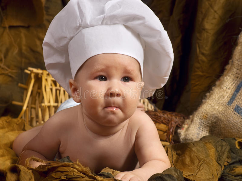 Kind tragender Kochenhut stockbilder