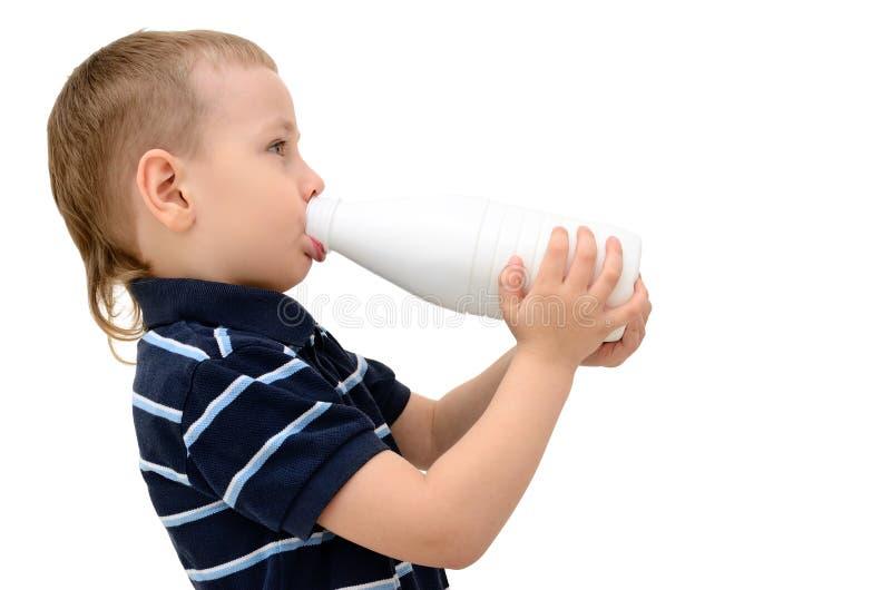 Kind trinkt Milch von einer Flasche auf einem weißen Hintergrund lizenzfreies stockbild