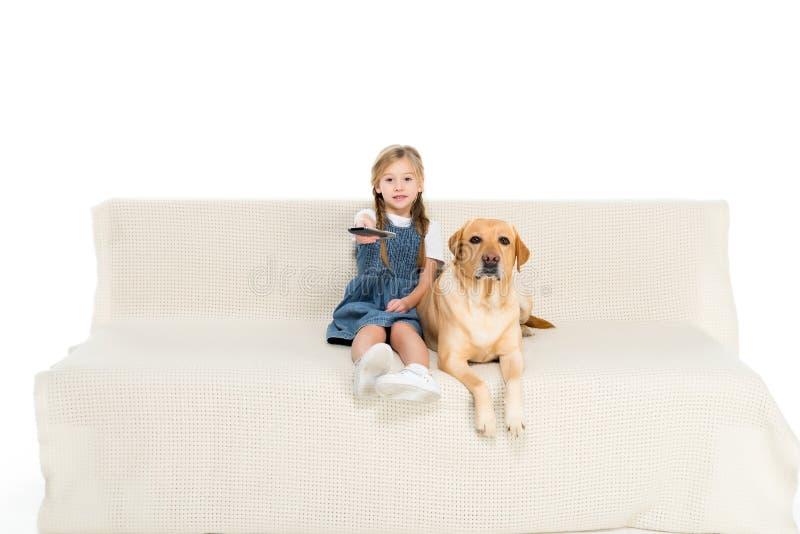 Kind und Hund, die auf Sofa fernsehen, stockbild