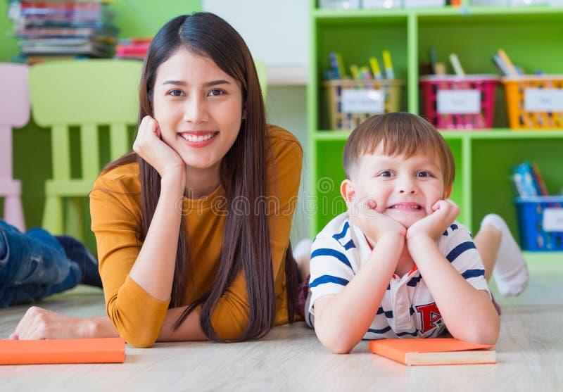 Kind und Lehrer, die Kamera betrachten und L?cheln, das unten in der Schule Bibliothek liegt Fu?boden Kindergarten, der Schule le lizenzfreie stockfotos