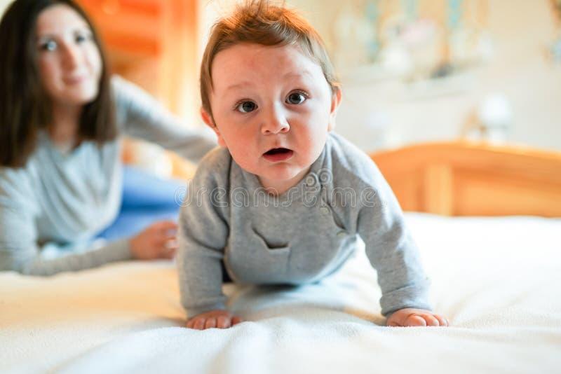 Kind und Mutter auf Bett Mutter und Baby, die im sonnigen Schlafzimmer spielen Elternteil und Kleinkind, die sich zu Hause entspa lizenzfreies stockfoto
