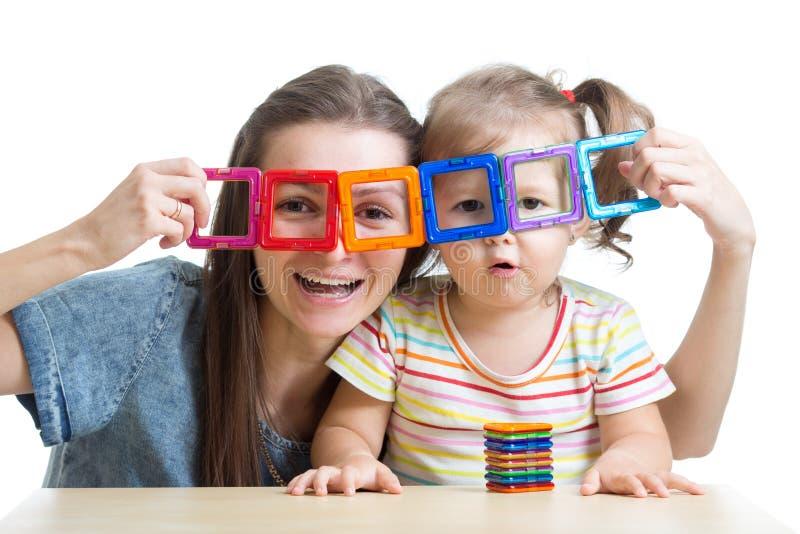 Kind und Mutter, die mit magnetischem Erbauer spielen stockbild