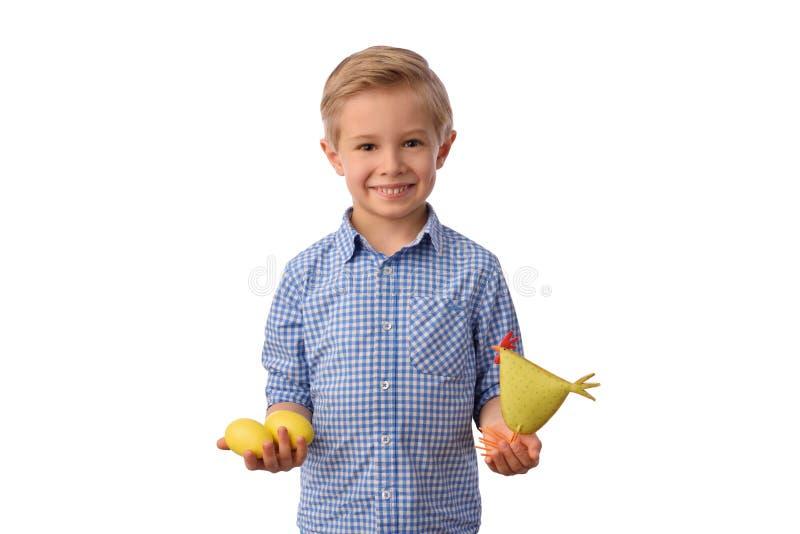 Kind und Ostern Der lächelnde blonde Junge, 6 Jahre alt, hält gelbe Hühner stockfotografie