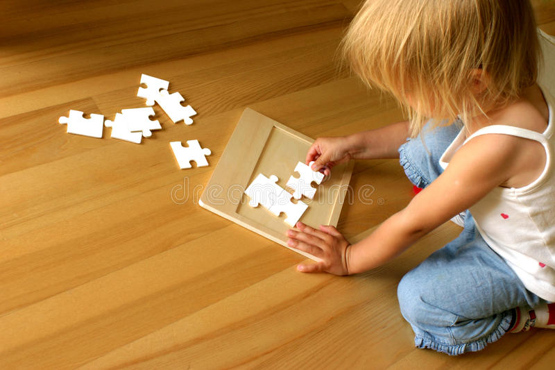 Kind und Puzzlespiel lizenzfreies stockfoto