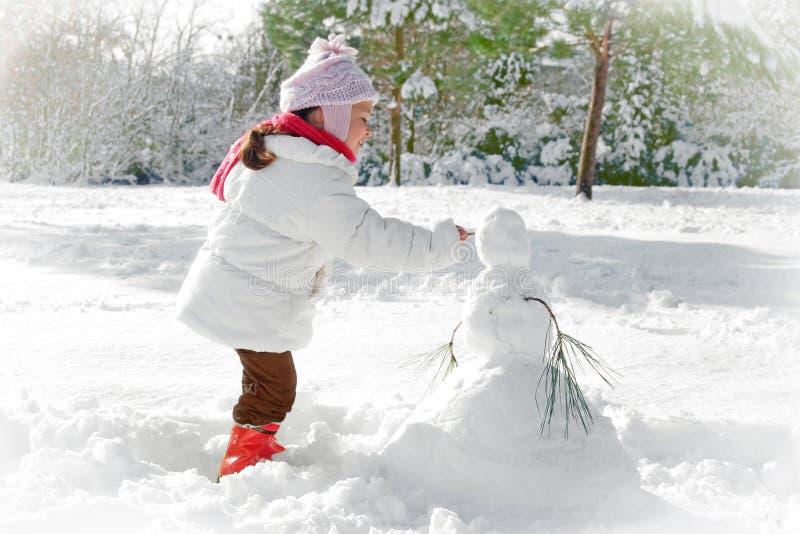 Kind und Schneemann lizenzfreie stockfotos