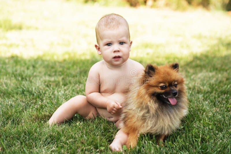 Kind und Welpe auf dem grünen Gras draußen stockfotografie