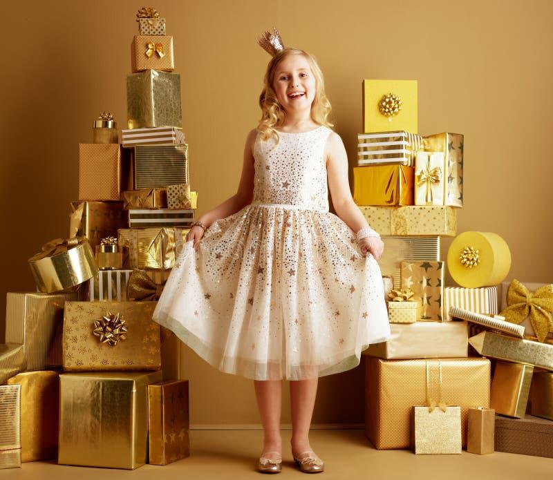 Kind unter 2 Stapel von goldenen Geschenken vor einfacher Wand stockfotografie