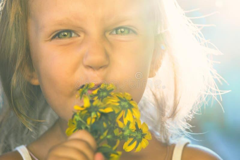 Kind van een klein meisje die met grote mooie ogen bloemen snuiven royalty-vrije stock foto