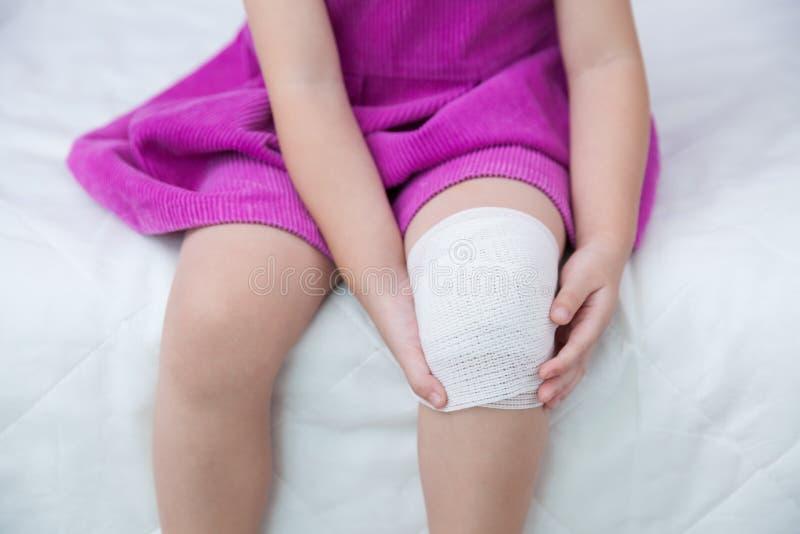 Kind verletzt Wunde auf dem Knie des Kindes mit Verband lizenzfreie stockfotos