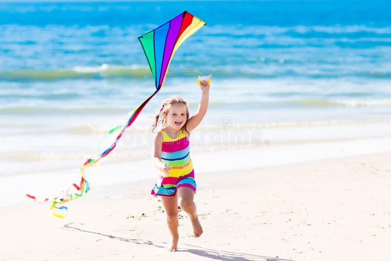 Kind vliegende vlieger op tropisch strand stock afbeelding
