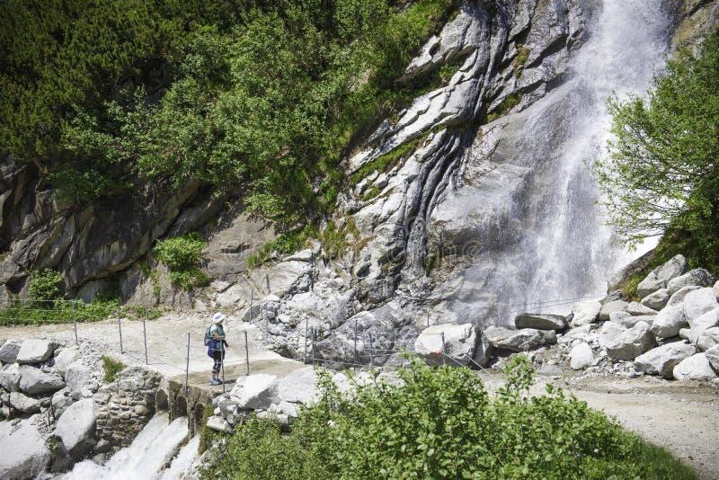 Kind vor einem großen Wasserfall durch den Stein lizenzfreie stockfotos