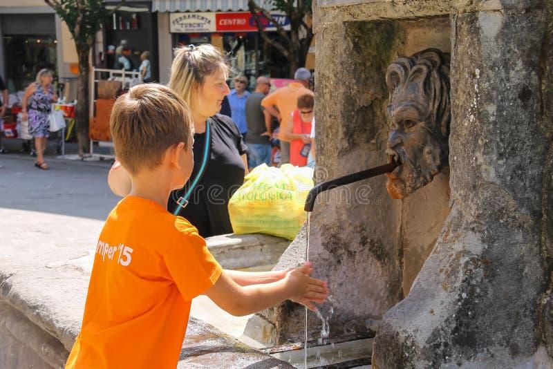 Kind wäscht seine Hände unter Straßenhahn in Fanano, Emilia Romagna, Italien stockfoto