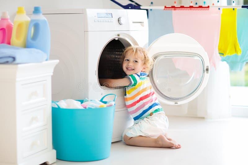 Kind in wasserijruimte met wasmachine stock foto