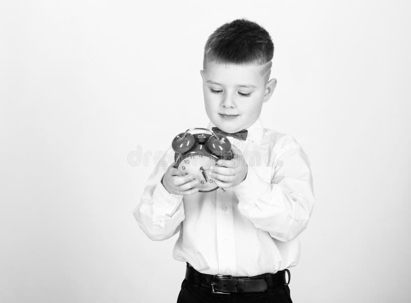 Kind weinig rode klok van de jongensgreep Het is tijd Programma en timing Ochtendroutine Schooljongen met wekker kid stock fotografie