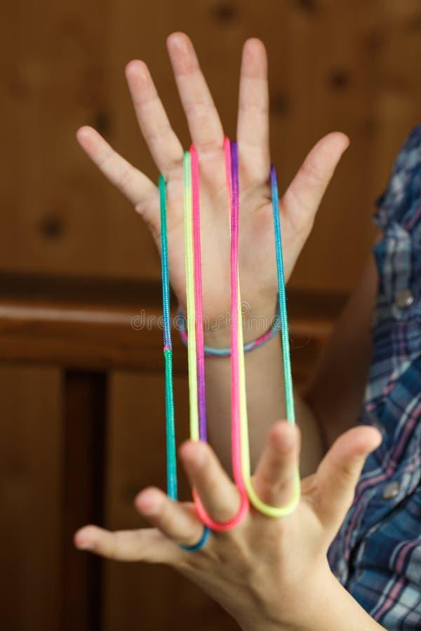 Kind, welches das klassische Schnurspiel, Formen schaffend spielt stockbild