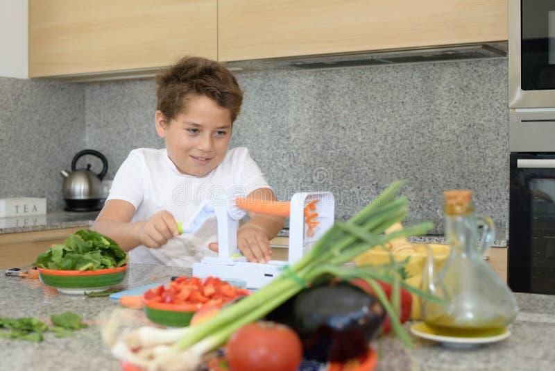 Kind, welches das Mittagessen vorbereitet Ausschnittkarotten lizenzfreie stockfotografie