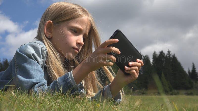 Kind, welches das Tablet im Freien im Park, Kindergebrauch Smartphone auf Wiesen-Mädchen im Gras spielt stockbilder