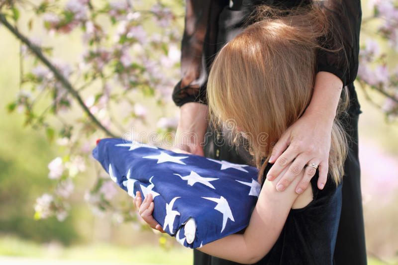 Kind, welches die gefaltete amerikanische Flagge einer Muttergesellschafts anhält