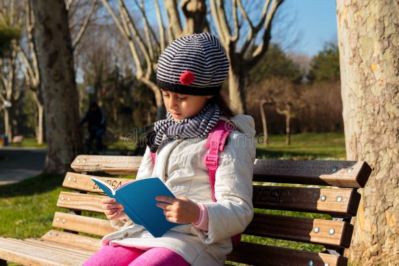 Kind, welches draußen das Buch im Park liest stockbilder