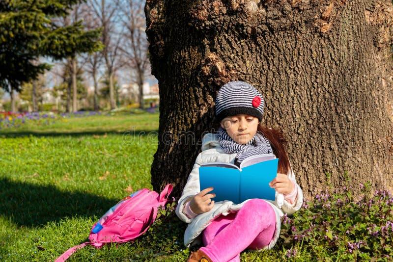 Kind, welches draußen das Buch im Park liest lizenzfreies stockbild