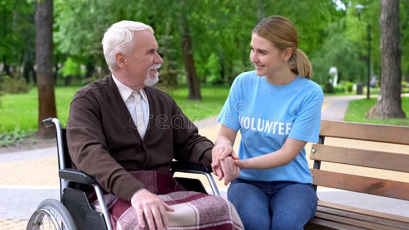 Kind young woman volunteer t-shirt holding disabled male hand, patient support stock photos