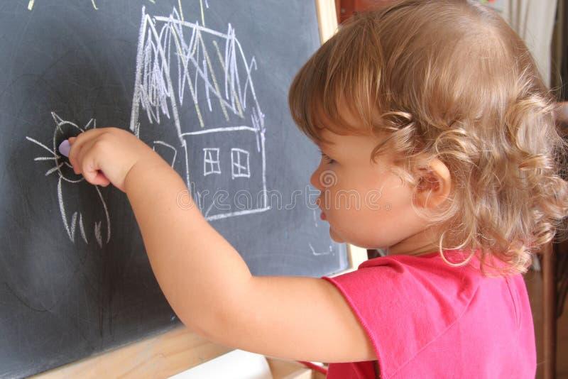 Kind zeichnet auf die Tafel stockfotos