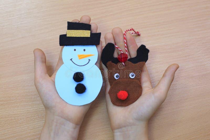 Kind zeigt ein Filz Weihnachtsbaumspielzeug Kind hält ein Weihnachtsspielzeug in seiner Hand Einfaches Winterhandwerk und -tätigk stockfoto