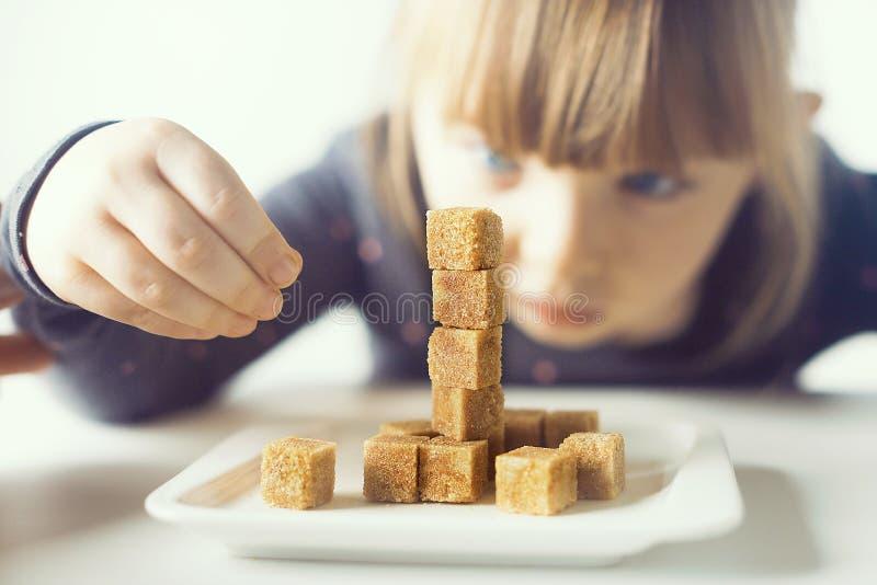 Kind, Zuckerwürfel Problem des übermäßigen Verbrauchs des Zuckers durch Kinder unter dem Alter von 10 Jahren lizenzfreies stockfoto