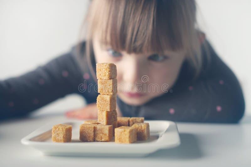 Kind, Zuckerwürfel Problem des übermäßigen Verbrauchs des Zuckers durch Kinder unter dem Alter von 10 Jahren lizenzfreies stockbild