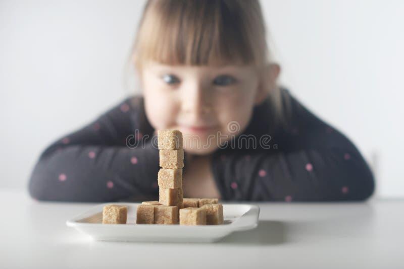 Kind, Zuckerwürfel Problem des übermäßigen Verbrauchs des Zuckers durch Kinder unter dem Alter von 10 Jahren stockbilder