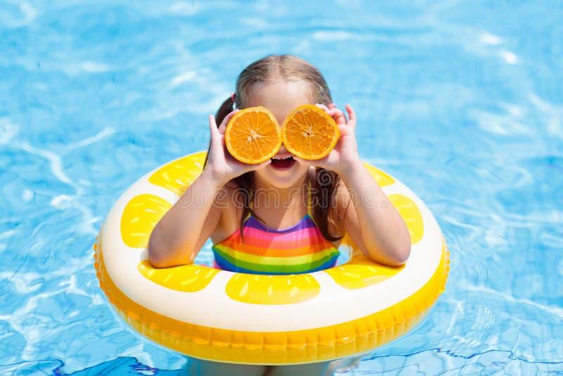 Kind in zwembad Jong geitje dat sinaasappel eet royalty-vrije stock afbeelding