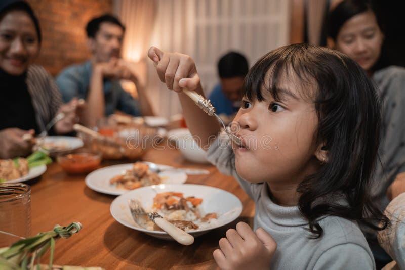Kinddochter die zelf tijdens diner eten royalty-vrije stock foto