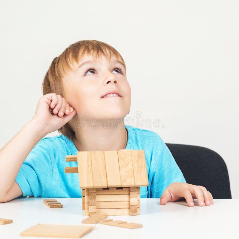 Kinddromen over familiehuis Het stuk speelgoed blokkeert huis Weinig jongen bouwt klein blokhuis Concept 6 van onroerende goedere stock afbeelding