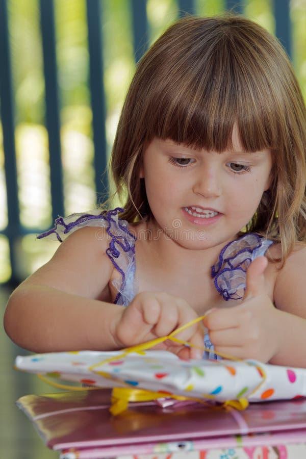 Kinderöffnendes Geschenk lizenzfreie stockfotos