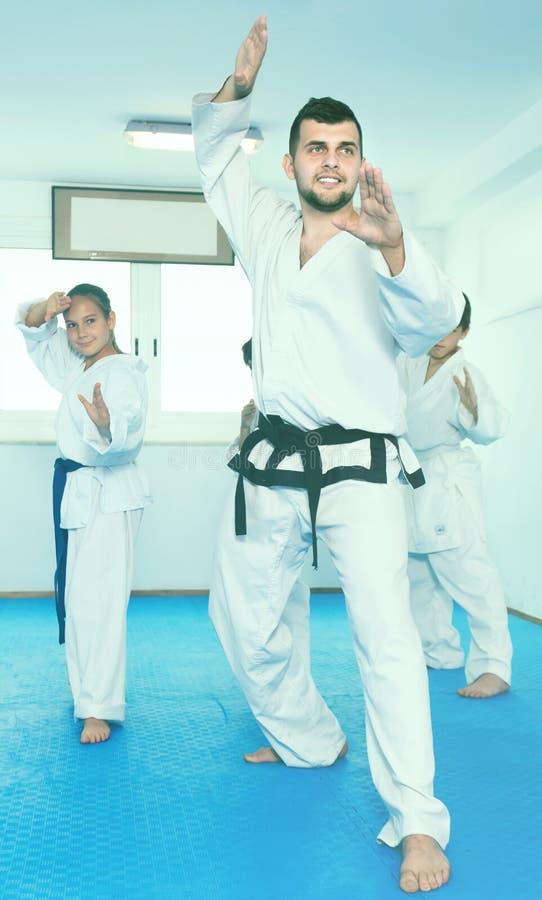 Kinderüben neue Bewegungen mit Trainer stockfotos