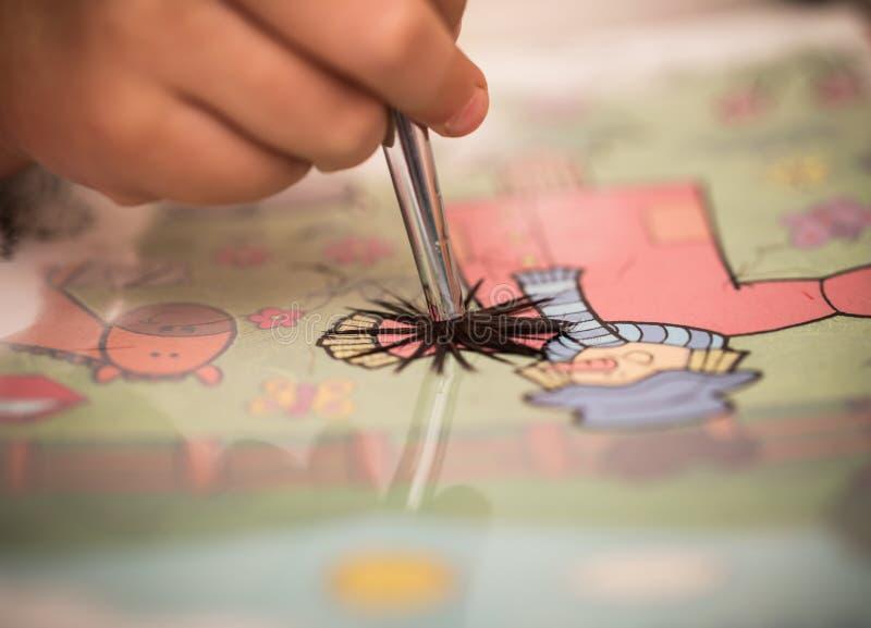 Kinder übergeben mit Farben einer Bürste auf Weißbuch lizenzfreie stockfotografie