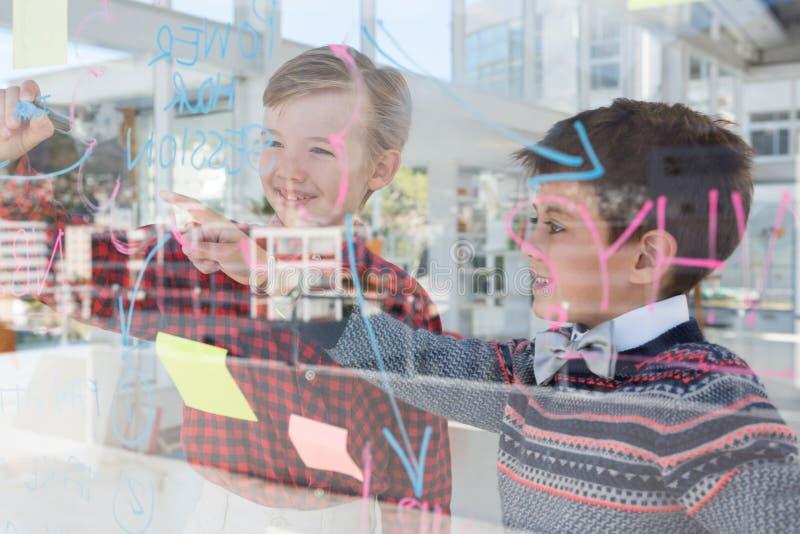 Kinder als Unternehmensleiter, die über whiteboard sich besprechen lizenzfreie stockfotografie