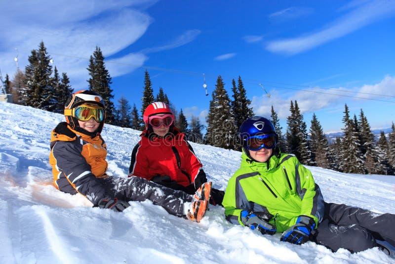 Kinder auf einer schneebedeckten Steigung lizenzfreie stockbilder