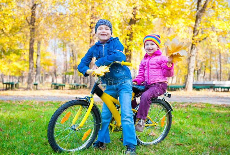 Kinder auf Fahrrad im Herbstpark lizenzfreie stockfotografie