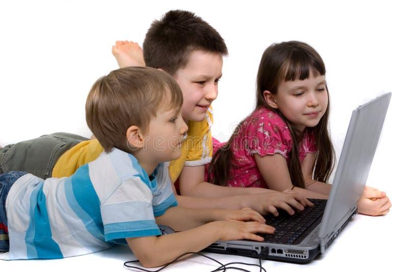 Kinder auf Fußboden mit Laptop-Computer stockfotos